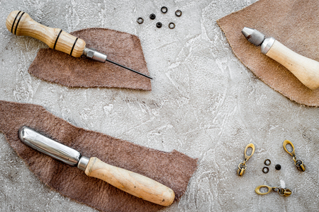 Leather craft. Tanners tools on grey stone background top view copyspace