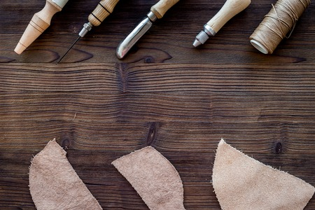 Leather craft. Knife, awl and other tools on dark wooden background top view. Stock Photo