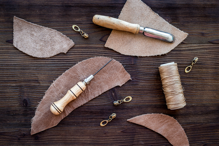 Leather craft accessories. Tools and matherials on dark wooden background top view Zdjęcie Seryjne