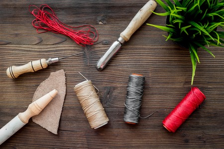 Leather craft workshop. Tools on dark wooden table background top view