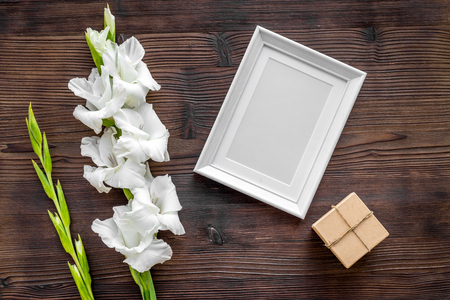 Blank photo frame near flower gladiolus on dark wooden background top view mockup Stock fotó