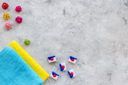 Laundry. Bars of dry detergent near clean towel on grey stone background top view copyspace Stock Photo