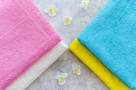 Fresh towel after washing on grey stone background top view