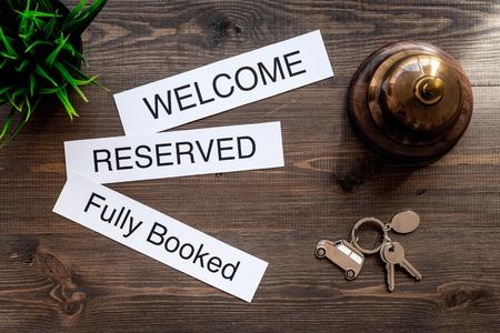 Bij het hotel. Woorden welkom, volgeboekt, gereserveerd op donker houten tafel bovenaanzicht Stockfoto