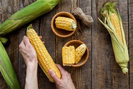 Womans hands clean corn cob. Rustic wooden background top view