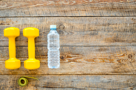 Fitness for loosing weight. Dumbbells, measure tape and water on wooden background top view copyspace