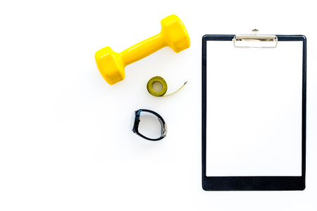 Fitness for losing weight. Dumbbells, fitness bracelet, measure tape on white background top view copyspace mockup