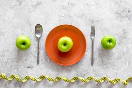 Slimming diet. Apple at plate and measuring tape on grey stone background top view
