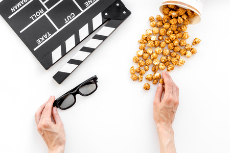 filmmaker: To go to the cinema. Clapperboard, glasses and popcorn on white background top view