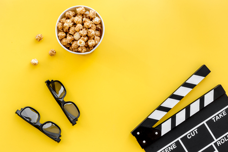 Ready to watch film. Clapperboard, glasses and popcorn on yellow background top view copyspace Stock Photo