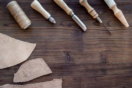 Lederhandwerk. Messer, Ahle und andere Werkzeuge auf dunklem Holz Hintergrund Draufsicht copyspace