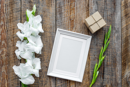 Blank photo frame near flower gladiolus on rustic wooden background top view.