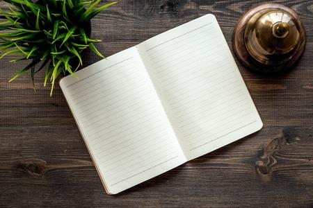 Hotel boeken. Dienstbel en notitieboekje bij de ontvangst op het donkere houten model van de lijstbovenkantmening Stockfoto
