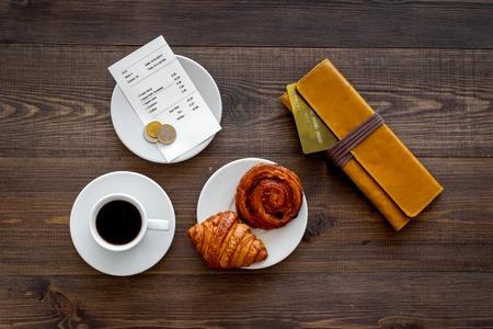 カフェでカードで料金を支払います。コーヒーとクロワッサン暗い木製テーブル トップ ビューで近くの財布、ビル、銀行カード。
