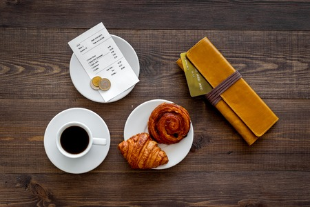 Pay bill at cafe by card. Purse, bill and bank card near coffee and croissant on dark wooden table top view. Imagens