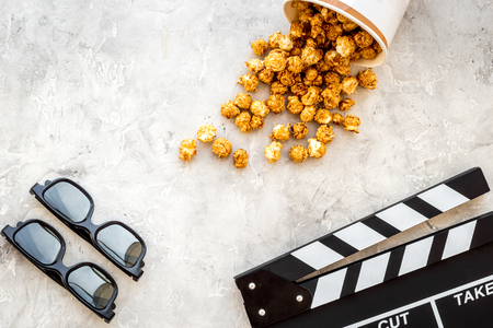 filmmaker: Watching film. Clapperboard, glasses and popcorn on grey background top view.