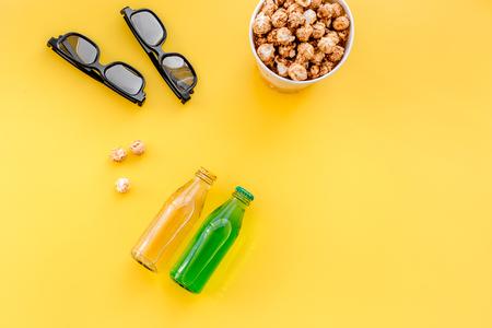 Des collations pour regarder des films au cinéma. Popcorn et soda près de verres sur fond jaune copyspace vue de dessus Banque d'images - 84057747
