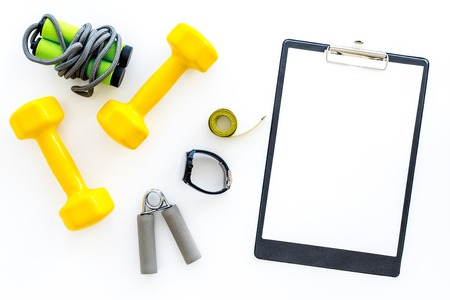 Fitness for loosing weight. Dumbbells, jump rope and measure tape on white background top view.