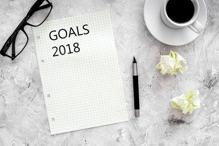 Goals list for 2018. Sheet of paper near pen, glasses and cup of coffee on grey stone background top view mockup