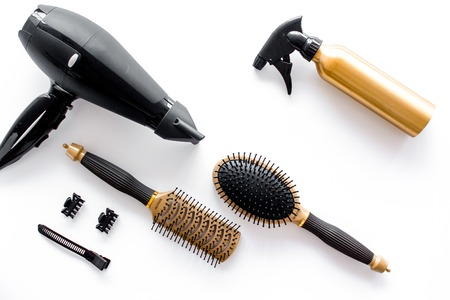 Hairdryer and hairdresser tools in beauty salon on white background top view copyspace
