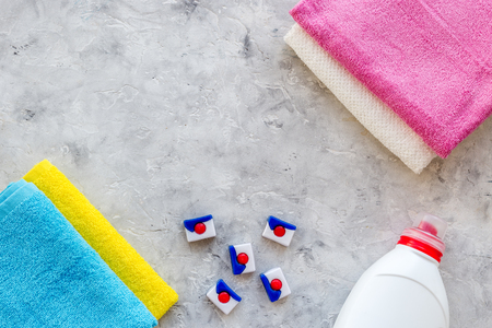 Laundry. Dry and liquid detergents near clean towel on grey stone background top view copyspace Stock Photo - 84117319