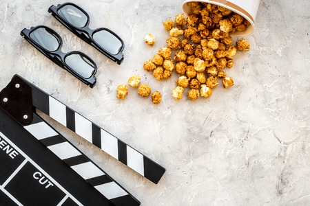 Watching film in the cinema. Clapperboard, glasses and popcorn on grey background top view copyspace