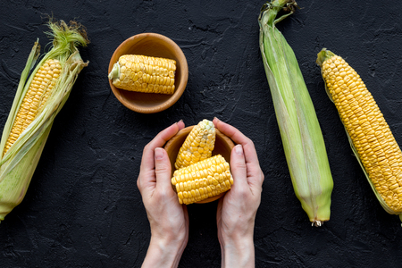 Womans hands clean corn cob. Black stone background top view