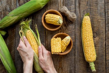 Womans hands clean corn cob. Black stone background top view.
