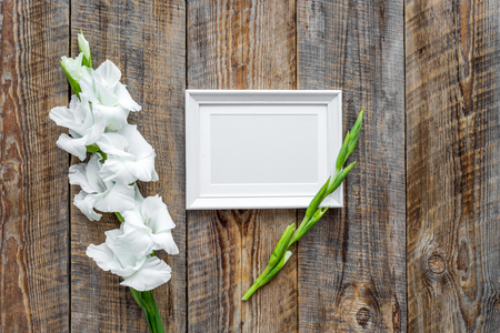 Blank photo frame near flower gladiolus on rustic wooden background top view. Stock fotó - 84229503