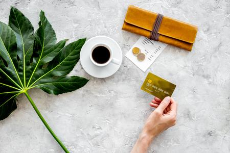 식당에서 계산서를 지불하십시오. 손을 빌, 은행 카드 및 동전 근처 커피를 잡아. 회색 돌 테이블 상위 뷰입니다.