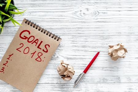 Haga una lista de objetivos para 2018. Vista superior del cuaderno, pluma y hojas arrugadas de papel.