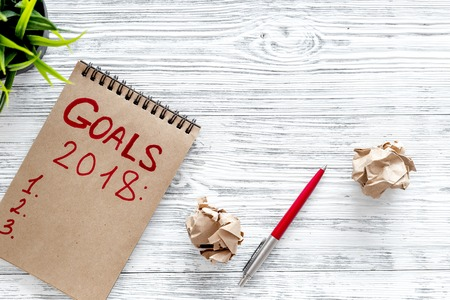 Make a goals list for 2018. Notebook, pen and wrinkled sheets of paper background top view. Stok Fotoğraf - 84230166