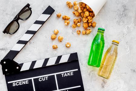 Nourriture pour regarder un film. Pop-corn et soda près de Clap, lunettes sur la vue de dessus de fond gris. Banque d'images - 84230516