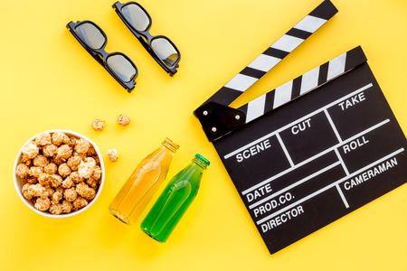 Des collations pour regarder des films. Popcorn et soda près de clapperboard, verres sur la vue de dessus de fond jaune. Banque d'images - 84230715