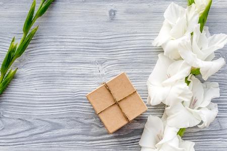 축하 액세서리. 빛 나무 테이블 상위 뷰 copyspace에 꽃 gladiolus 근처 크 라프 트 종이 상자