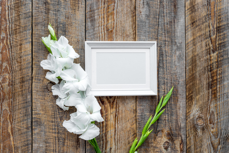 Blank photo frame near flower gladiolus on rustic wooden background top view mockup copyspace