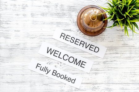 At the hotel. Words welcome, fully booked, reserved on light wooden table top view copyspace Stok Fotoğraf - 84326239