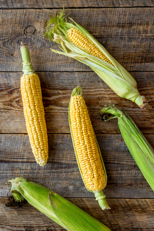 Vegetarian food. Corn cobs on rustic wooden background top view Stock Photo