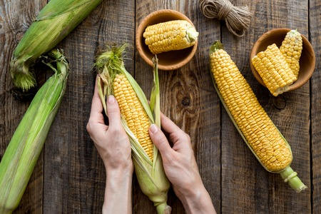 Womans hands clean corn cob. Rustic wooden background top view