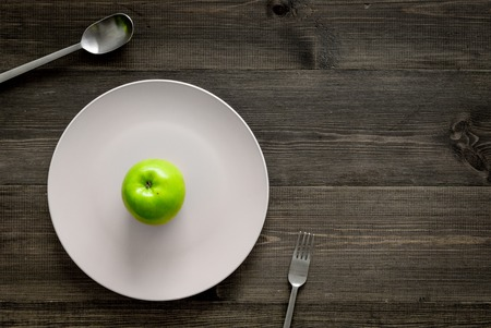 Slimming diet. Apple at plate on wooden background top view copyspace