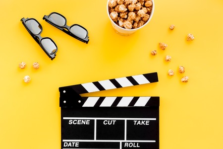 filmmaker: Ready to watch film. Clapperboard, glasses and popcorn on yellow background top view