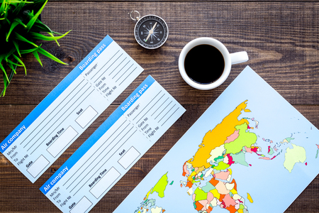 Accessories for traveling with tickets, map and cup of coffee on office desk dark wooden background top view