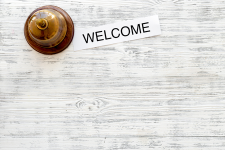 Check in at the hotel. Word welcome near service bell on light wooden table background top view.