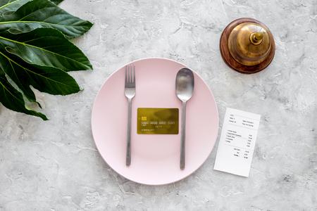 카페에서 계산서를 요청하십시오. 서비스 벨 회색 돌 테이블 상위 뷰 빈 접시에 은행 카드 근처.