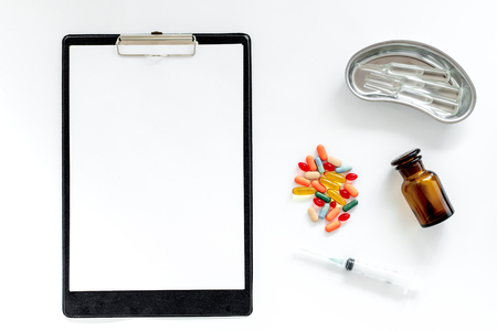 Doctors table. Clip pad, pills, syringe and cuvette with ampoulie on white background top view. Stok Fotoğraf