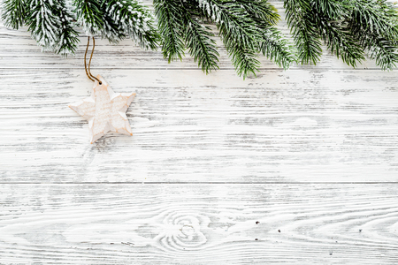 Christmas background. Toys and spruce branches on light wooden background top view.