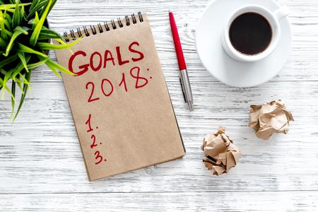 Maak een doelstellingenlijst voor 2018. Notitieboekje dichtbij pen en kop van koffie op grijze houten hoogste mening als achtergrond.