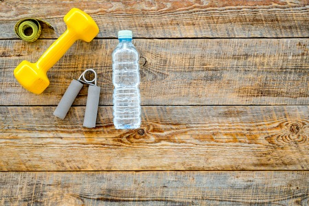 Fitness for losing weight. Dumbbells, expander, measure tape and water on wooden background top view. Stock Photo