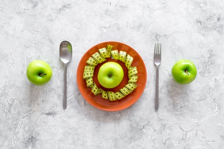 Slimming diet. Apple at plate and measuring tape on grey stone background top view. Stock Photo