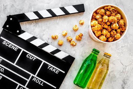Nourriture pour regarder un film. Pop-corn et soda près de Clap, lunettes sur la vue de dessus de fond gris. Banque d'images - 84404750
